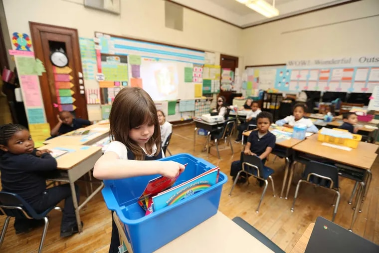 Juliana Tammela picks a donated book in Kim Robertson's first grade class at Crossen Elementary School. The organizing committee from this summer's Democratic National Convention is donating nearly $1 million to the Philadelphia School District's Right Books campaign, which places classroom libraries at elementary schools across the city, Friday December 16, 2016 ( DAVID SWANSON / Staff Photographer )