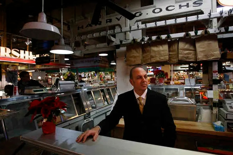 Nicholas Ochs stands behind the counter at the Reading Terminal Market stand where his father, Harry G. Ochs Jr., worked as a butcher for more than a half-century. Ochs died in 2009 at 80. He had taken over the stand from its original owner and changed his name for the business.