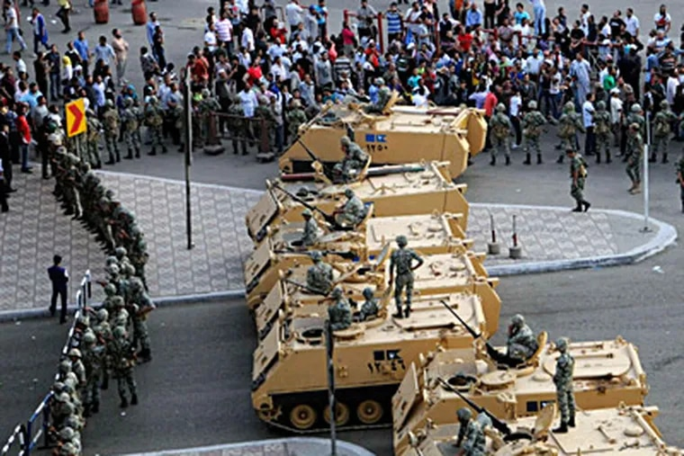 Military vehicles block the road outside the Defense Ministry in Cairo as troops attempt to stand their ground against protesters. Despite official warnings against gathering, groups that had been demonstrating in Tahrir Square converged on the area. AHMED HAMMAD / Associated Press