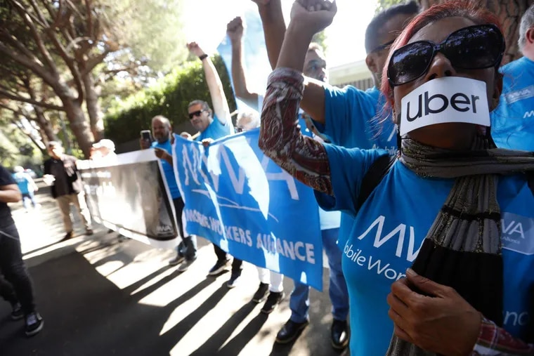 Uber and Lyft driver Teresa Mercado (right) joins members of the Mobile Workers Alliance, which consists of Uber and Lyft drivers, protesting at the home of Uber co-founder Garrett Camp in Beverly Hills.