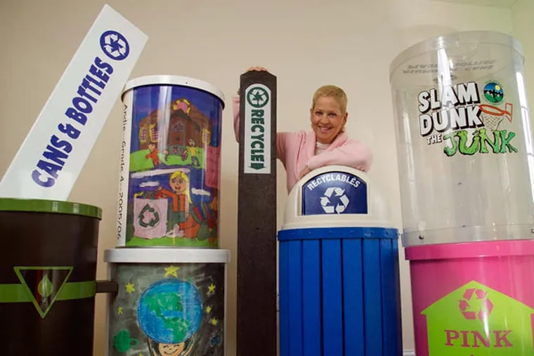 Bonnie Haas, president of Kettle Creek Corp., amid some of the recycling containers and signage her company makes.