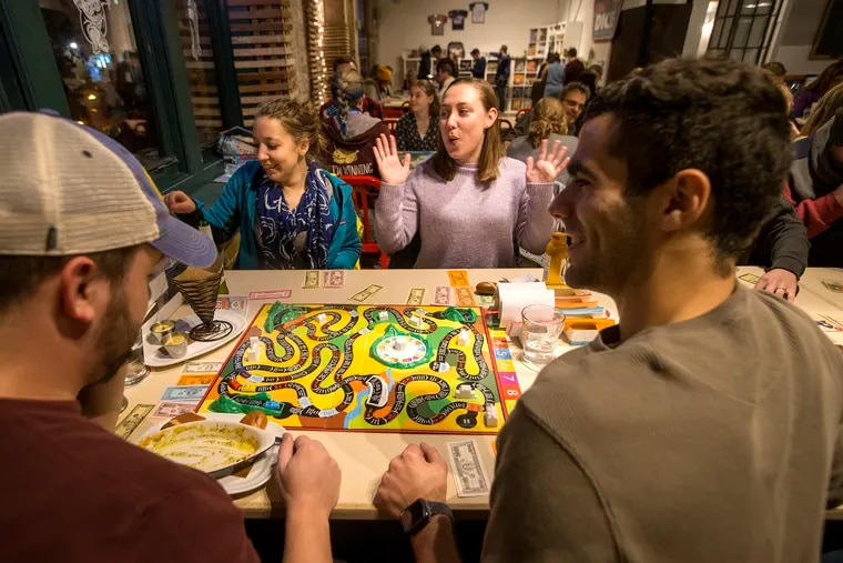 L-R: Zach Santo, Ashley Saybaugh, Liz Biron, and Shaun Dattola play The Game of Life at Thirsty Dice, a board game cafe, on Dec. 1, 2018.