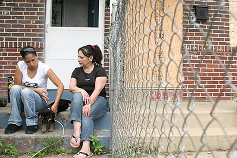Karen Cortez, 28, and her mother, Nancy Lopez, 53, sit on the front porch of their house in Mount Holly with their puppy, Scooby. (Neal Santos/Inquirer)