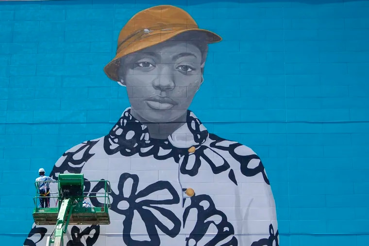 Arthur Haywood works to install a mural by Amy Sherald, the woman who painted the portrait of Michelle Obama for the Smithsonian, at 1109 Sansom in Center City Philadelphia on Wednesday, May 22, 2019. The girl in the mural, Najee Spencer-Young, is from North Philly.
