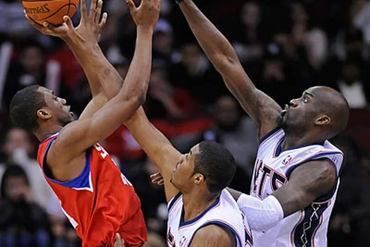 Thaddeus Young tried to shoot over Derrick Favors and Johan Petro during the second quarter. (Bill Kostroun/AP)