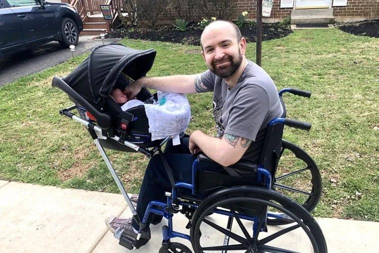 Jeremy King, 37, takes son Phoenix for a stroll using a car-seat connector that high school students in Maryland created for him.