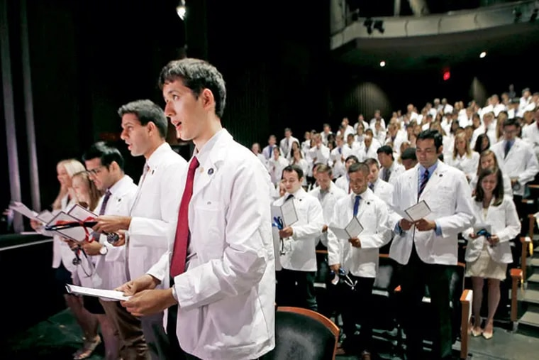 """First-year medical students at Penn's Perelman School of Medicine recite the Hippocratic oath during a """"white coat ceremony"""" in Zellerbach Theatre at the Annenberg Center."""