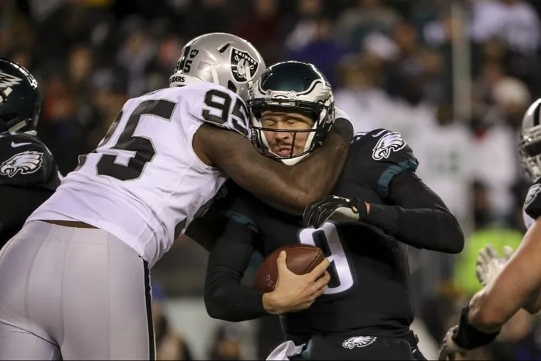 Eagles quarterback Nick Foles is sacked by Oakland Raiders defensive lineman Jihad Ward in the third quarter of the Eagles' 19-10 win Monday night.