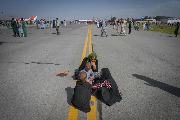 Afghan people sit along the tarmac as they wait to leave the Kabul airport on Aug. 16.