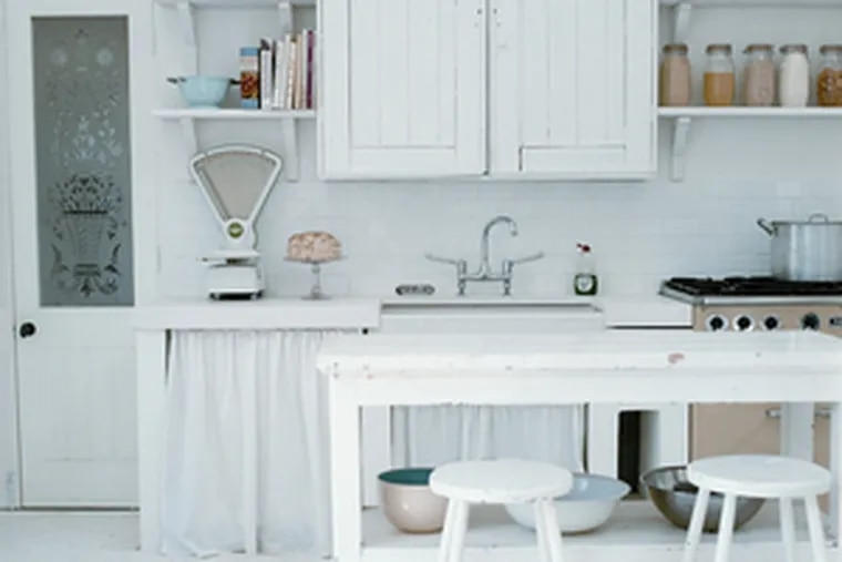 White unifies a kitchen furnished with flea-market finds, including old cabinets and a table set on wheels.