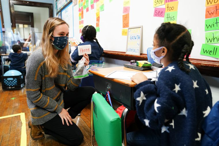 Student teacher Sophia Bonavolonta, left, works with reading flash cards with student Suhayla Stinette, 7, right, at Belmont Charter School, Thursday, February 25, 2021. Belmont Charter School started bringing K-2 students back to classrooms last week, this week it reopened for grades 3-5.