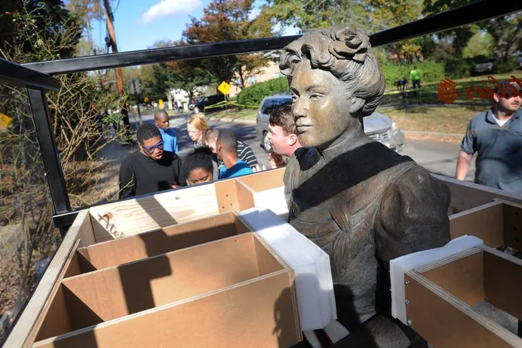 Students hover in the background as workers remove a sculpture of Margaret Bancroft, founder of the Bancroft school in Haddonfield, for transport to a new  campus in Mount Laurel that is scheduled to open in January. Tje bronze likeness was created by Judith B. Flicker, whose son was a Bancroft student.