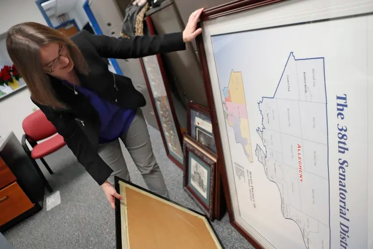 Pennsylvania state Senator-elect Lindsey Williams looks over a map and some photos as she settles into her new office in Glenshaw, Pa. (AP Photo/Keith Srakocic)