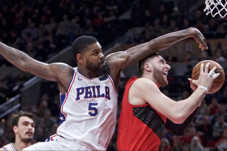 Trail Blazers center Jusuf Nurkic (right) gets fouled by the 76ers' Amir Johnson during the first half.