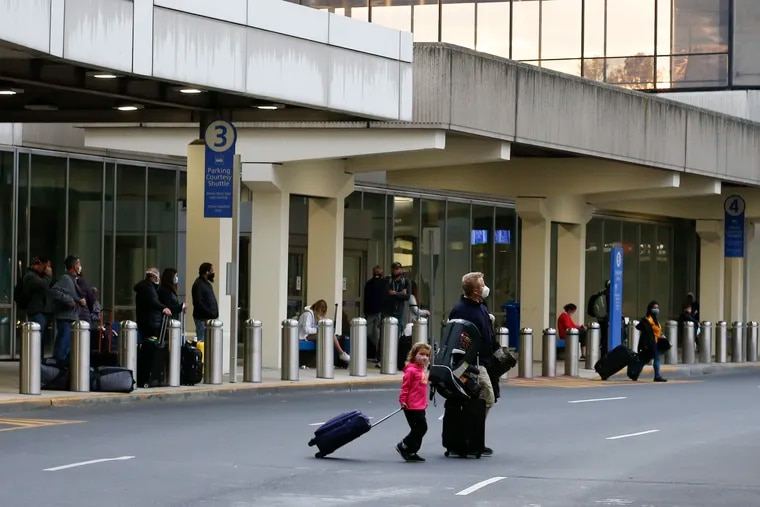 Travelers cross the street outside the pick-up area near the Terminal C baggage claim area at the Philadelphia International Airport on Friday, November 27, 2020.