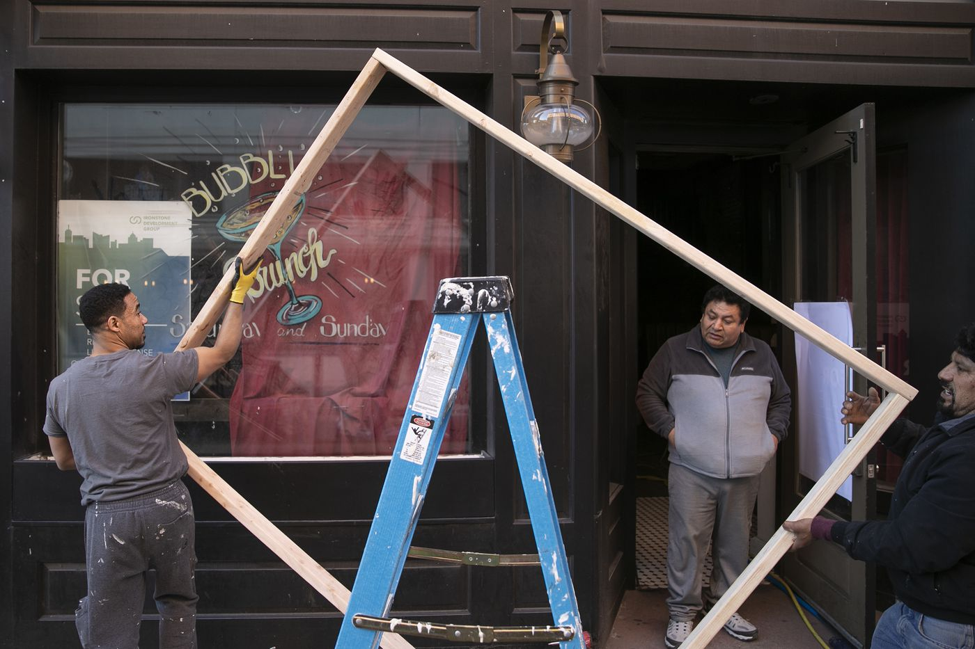 """Eduardo Saldana (center) of Philadelphia Custom Builders watches as his team boards up the popular Tinsel bar in Center City on Saturday. Gov. Tom Wolf called for the closure of all businesses that are not """"life-sustaining,"""" due to the spread of the coronavirus. Restaurants are now takeout or delivery only."""