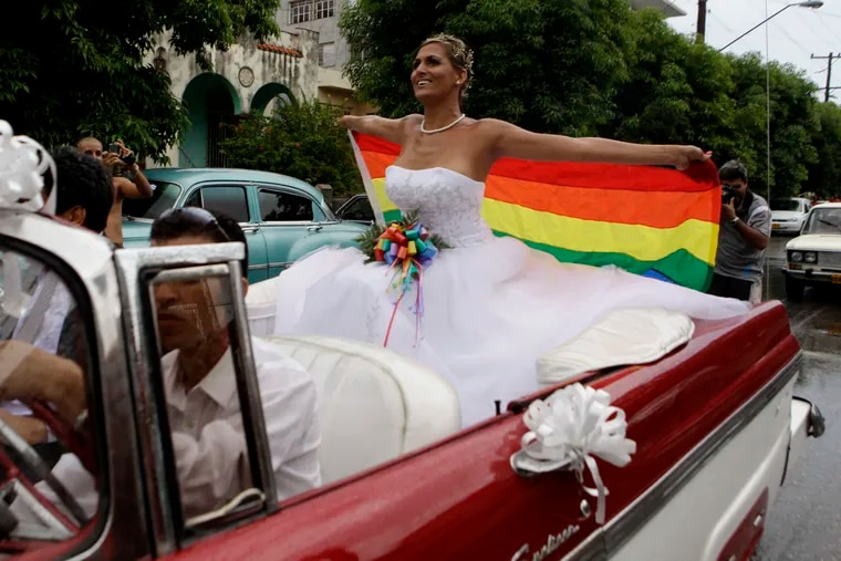 FILE - In this Aug. 13, 2011 file photo, holding up a gay pride flag, transsexual Wendy Iriepa, who had a sex change, rides to her wedding on a classic car in Havana, Cuba. Cuba said on Tuesday, Dec. 18, 2018 that language promoting the legalization of gay marriage will be removed from the draft of a new constitution after widespread popular rejection of the idea. (AP Photo/Javier Galeano, File)