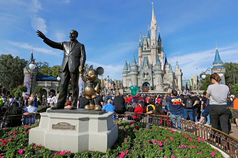 In this Jan. 9, 2019, file photo, guests watch a show near a statue of Walt Disney and Mickey Mouse in front of the Cinderella Castle at the Magic Kingdom at Walt Disney World in Lake Buena Vista, Fla.