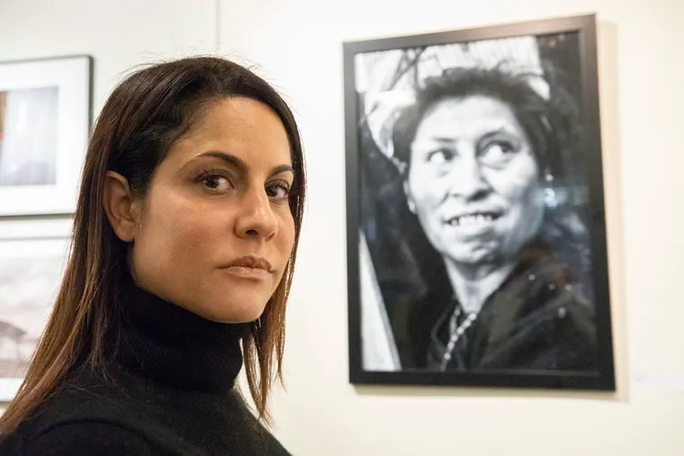 Ada Trillo, a Center City photographer, poses for a portrait in front of a photograph she made, which is part of an exhibit at the International House Philadelphia. Trillo has been documenting the migrant caravan in Mexico.
