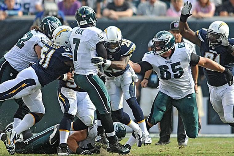 Eagles quarterback Michael Vick is hit as offensive lineman Lane Johnson watches. (Clem Murray/Staff Photographer)