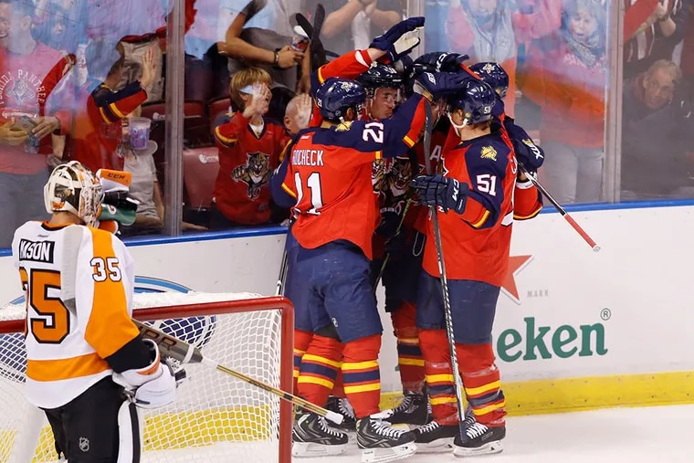Florida Panthers right wing Reilly Smith (center) is mobbed by teamates after his goal past Flyers goalie Steve Mason (35) in the first period at BB&T Center.