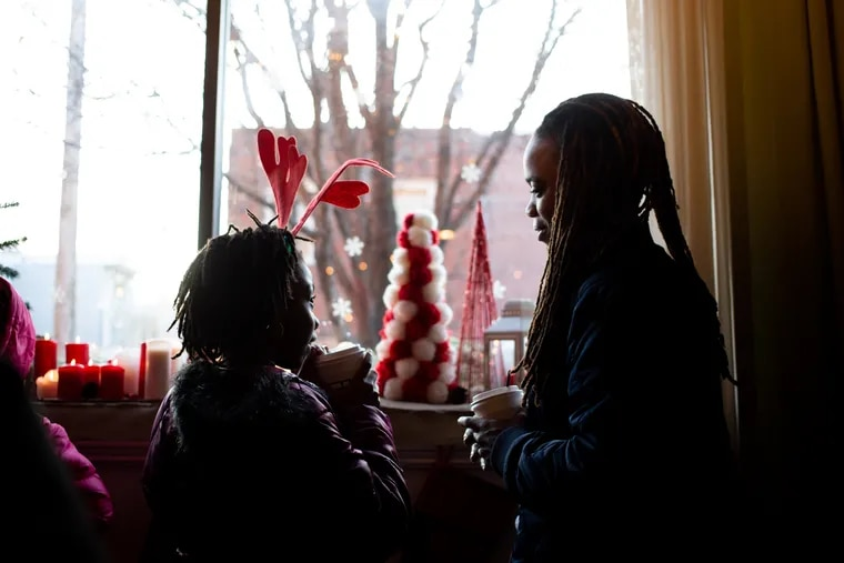 Shaleah Allen, 10, and her step-mother, Monique Woodland, look at Christmas decorations and discuss a gingerbread house they are going to decorate on Christmas eve at the Block Church in Port Richmond, December 24. Christmas often brings nostalgia and reflection, the writer says.