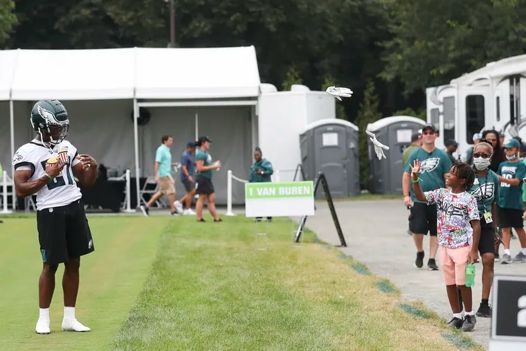 Eagles cornerback Zech McPhearson throws his gloves to fan while carrying Rita's water ice after the second day of training camp practice.