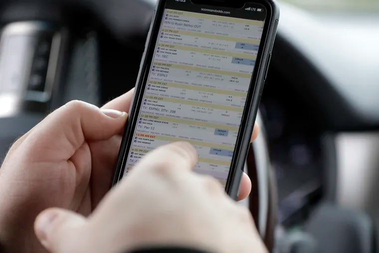 A New York bettor looks at betting lines for the day's sporting events before placing his bet in a parking lot just off the Bayonne Bridge, which divides New York and New Jersey. FanDuel, the leading online sports betting operation in New Jersey, announced Monday it has opened for business in Pennsylvania.