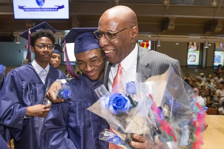 David Hardy (right), founder and CEO of Boys Latin of Philadelphia, is presented with blue roses by the Class of 2017 during graduation at Temple University. He is retiring.