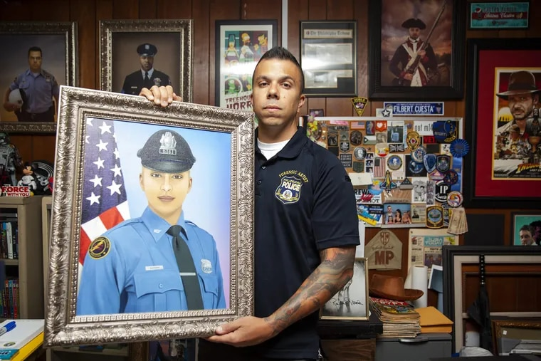 Officer Johnny Castro, a forensic composite artist for the Philly PD, poses for a portrait while holding a digital painting of Isabel Nazario, who died a year ago, at Philadelphia Police headquarters on Thursday, Sept. 06, 2018. Castro creates a digital portrait of police officers (including police dogs) who die in the line of duty around the U.S. and sends a copy for free to the family.