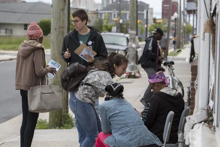 Thomas Meyer (2nd left) and Valentina Amaya (center leaning over), canvassers for Atlantic City Citizens Against the State Takeover (of the city's water department) meet city residents on North South Carolina Avenue May 24, 2017, asking them to sign petitions to prevent Gov. Christie from privatizing the water department. CLEM MURRAY / Staff Photographer