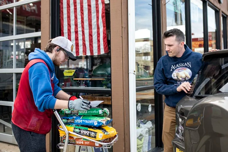 """Matt McConnell, 19, of Haddon Township, N.J., walks an order for Braden Reese, 27, of Haddon Township, N.J., in Haddon Township, N.J., on Saturday, March 21, 2020. Reese is doing home projects during the coronavirus outbreak and getting his lawn ready for the spring. """"Luckily, we are able to work from home,"""" Reese said. """"But my father already lost his job, and it's affecting [some] people more than others."""""""