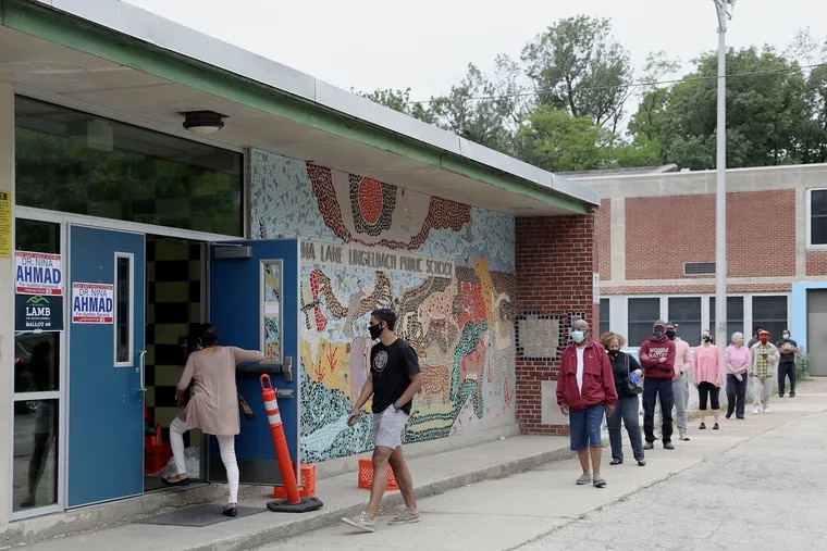 Voters line up outside Lingelbach Elementary School for Pennsylvania's primary in June. A national organization is planning to entertain voters waiting in line on Election Day on Nov. 3. They're launching the program this weekend in Philadelphia, taking a roving concert series to satellite election offices.