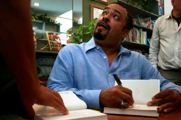 E. Lynn Harris signs a book at Giovanni's Room in 2006. The Philadelphia bookstore was one of the first to offer Harris a signing; later, when his works became best-sellers, the store was almost always a stop on his book tours.