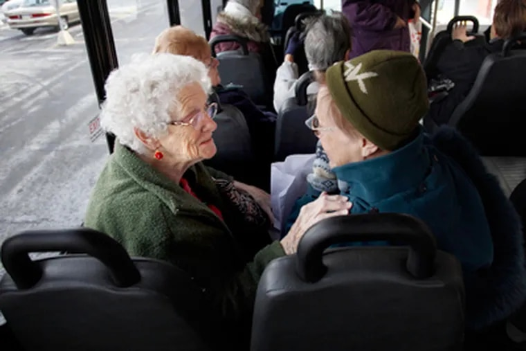 Emily Wilkinson (left) and Helene Basas greet each other as they find their seats on Abington's fixed-route bus for senior citizens. (Laurence Kesterson / Staff Photographer)