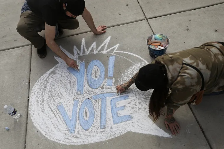 Michael Raspa (left) and Lawren Alice work on a chalk drawing encouraging people to vote outside Love Park in Philadelphia on Oct. 24.