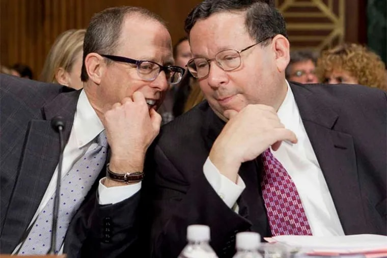 Comcast's David L. Cohen and Randal Milch, of Verizon Communications, speak before testifying at a 2012 hearing on a deal between the companies. (Andrew Harrer / Bloomberg)
