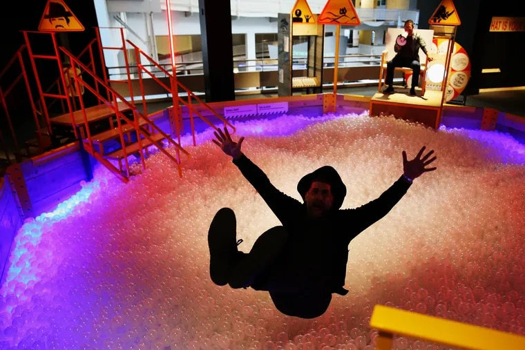 """David Borgenicht demonstrates falling into a ball pit in the """"Worst Case Scenario"""" exhibit at the Franklin Institute, based on the Quirk Books series."""