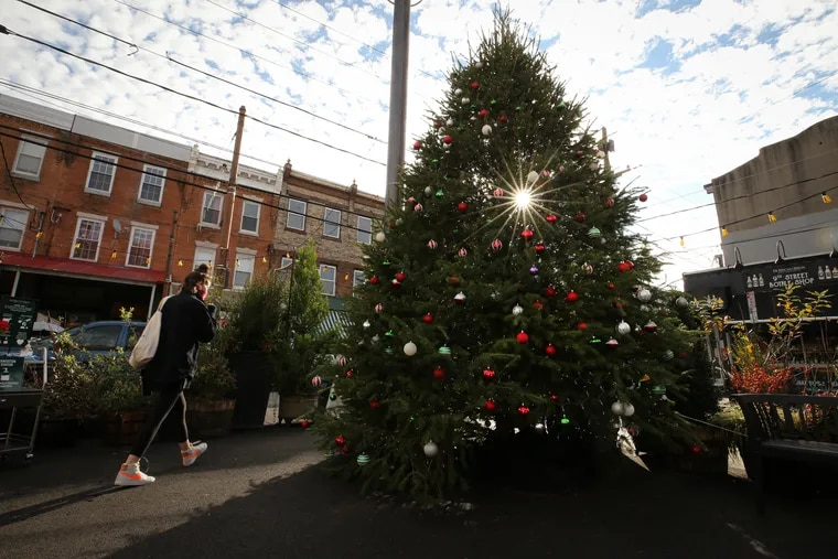 A customer passes a Christmas tree at the Piazza Di Bruno's Holiday Market along Ninth Street in Philadelphia's Italian Market Wednesday. The outdoor market was put in place to help cope with the restrictions due to the coronavirus pandemic.