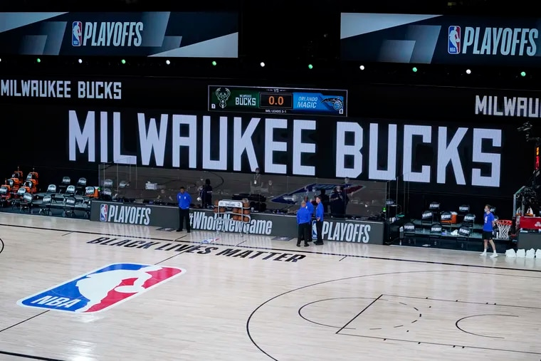 Officials stand beside an empty court on Wednesday after the game between the Milwaukee Bucks and Orlando Magic was postponed. The players are protesting racial injustice and the shooting on Sunday of Jacob Blake in Wisconsin.