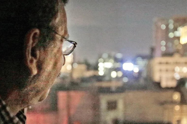 Allan Stein looks out of the guest bedroom window at his Washington Square West apartment on Feb. 4, 2015. His north-facing windows now overlook the new flashing neon sign on the Lits building. ( ELIZABETH ROBERTSON / Staff Photographer )
