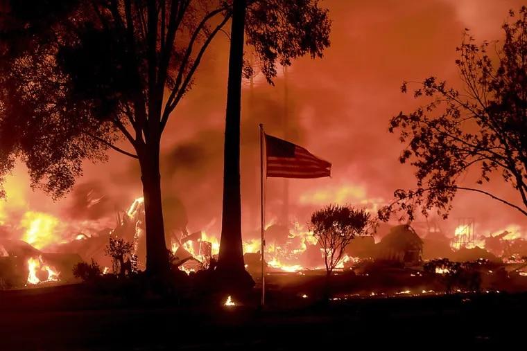 An American flag still flies as structures burn in Coffey Park, Calif.