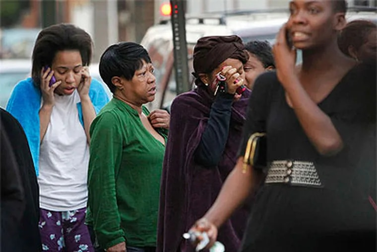 Neighbors of those who lost their lives in the early morning fire gather near the site, in shock, in tears, and spreading the word by phone. (Alejandro A. Alvarez / Staff Photographer)