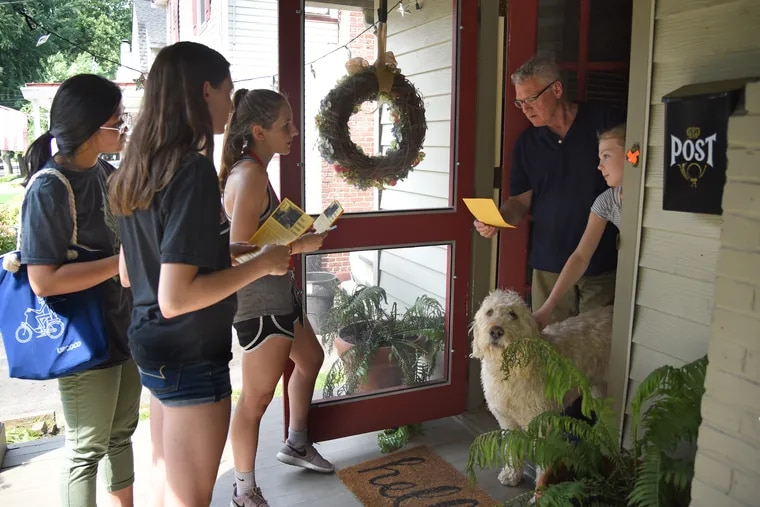 Haddonfield Memorial High School rising senior Kathleen Lee (from left), rising sophomore Sarah Naticchia , and her sister, rising senior Natalie Naticchia, go door to door canvasing in Haddonfield June 18, 2018. They talk with resident John Killkelly, with his daughter, Chloe Killkelly, 12, and their labradoodle, Henry. After reading the memoir of a former child soldier, the students are crowdfunding almost $50,000 to bring Garang Buk Buk, a South Sudanese former child soldier, to the U.S. to earn a Master's degree at Emory University.