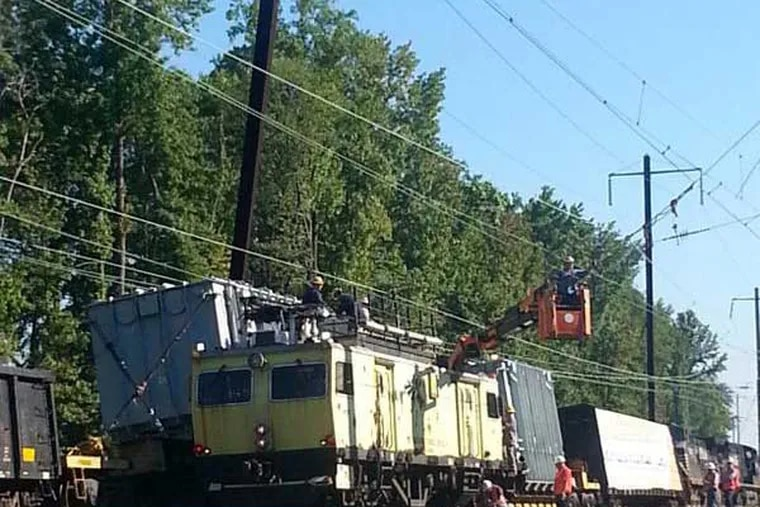 Amtrak crews make repairs to downed wires, caused by a freight train striking a support pole. (Photo from @AmtrakNEC on Twitter)