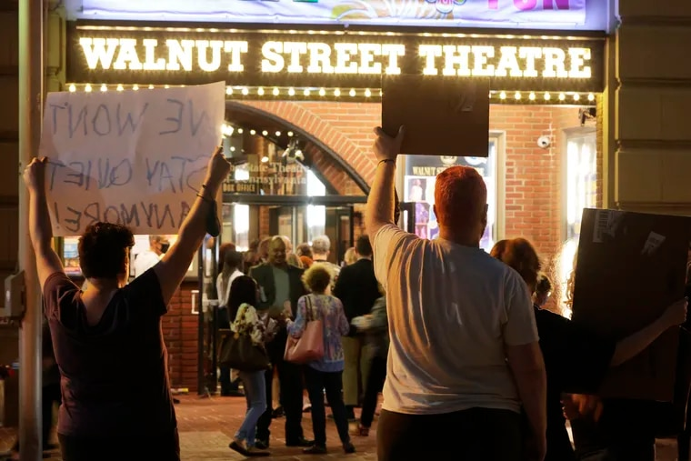"""Melissa Amilani (left), Brendan Little and Kate Henderson demonstrate along with other theatre performers and community members across the street from the Walnut Street Theatre's opening night performance of """"Beehive.""""  in Phila., Pa. on Oct. 6, 2021."""