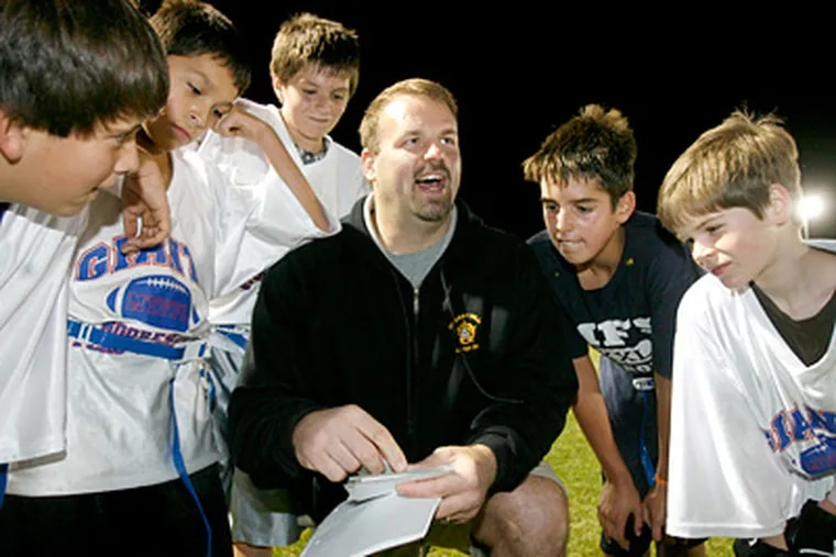 Jon Runyan huddles with his son Daniel (second from right) and other players on his flag football team. The former Eagles offensive lineman co-coached the team this year until the San Diego Chargers called. (Charles Fox / Staff Photographer )