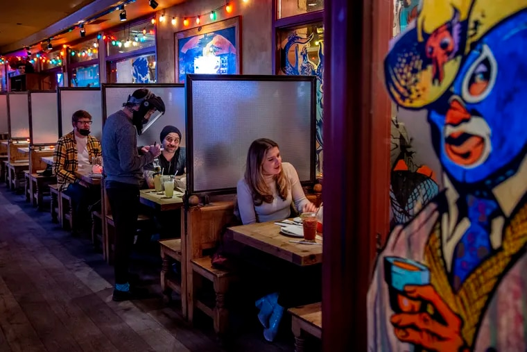 Waiter Tyler Waddle serves Gerard Gall and his party inside the El Camino Real Restaurant in Northern Liberties Nov. 19, 2020, on the last night before Philly's ban on indoor dining took effect. Pennsylvania is now considering a statewide ban.