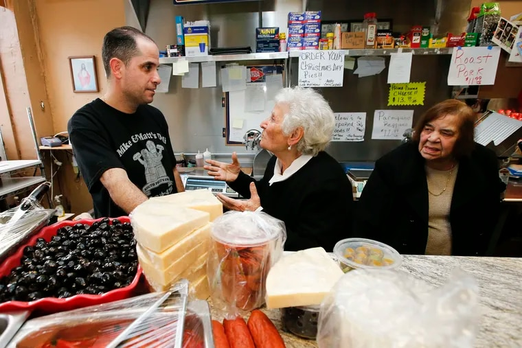 Matt Silvano, Girolama Giambri (center), and Flavia Carabello stand behind the counter at Matt and Mike's Italian Deli in South Philadelphia, where four generations of owners met to celebrate the place's anniversary.