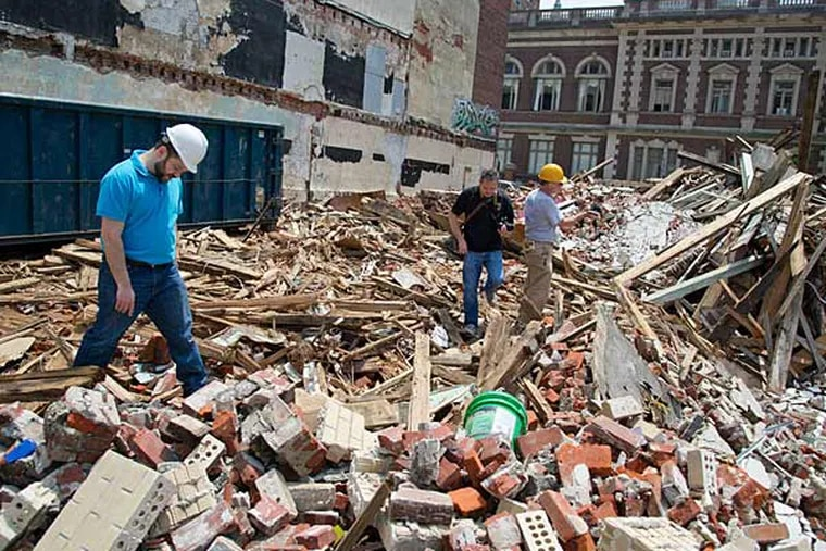 Attorney Jonathan Cohen (left) and a team of investigators search through the rubble of the building collapse at 22nd and Market Sts. searching for clues and evidence on June 9, 2013.  Cohen represents Linda Bell.  ( CLEM MURRAY / Staff Photographer )